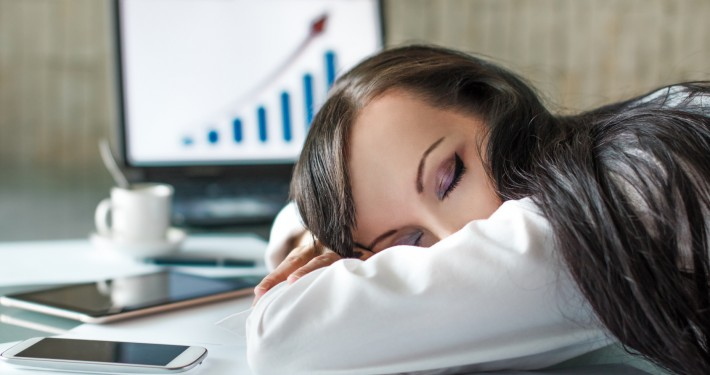 Tired businesswoman at desk during overtime
